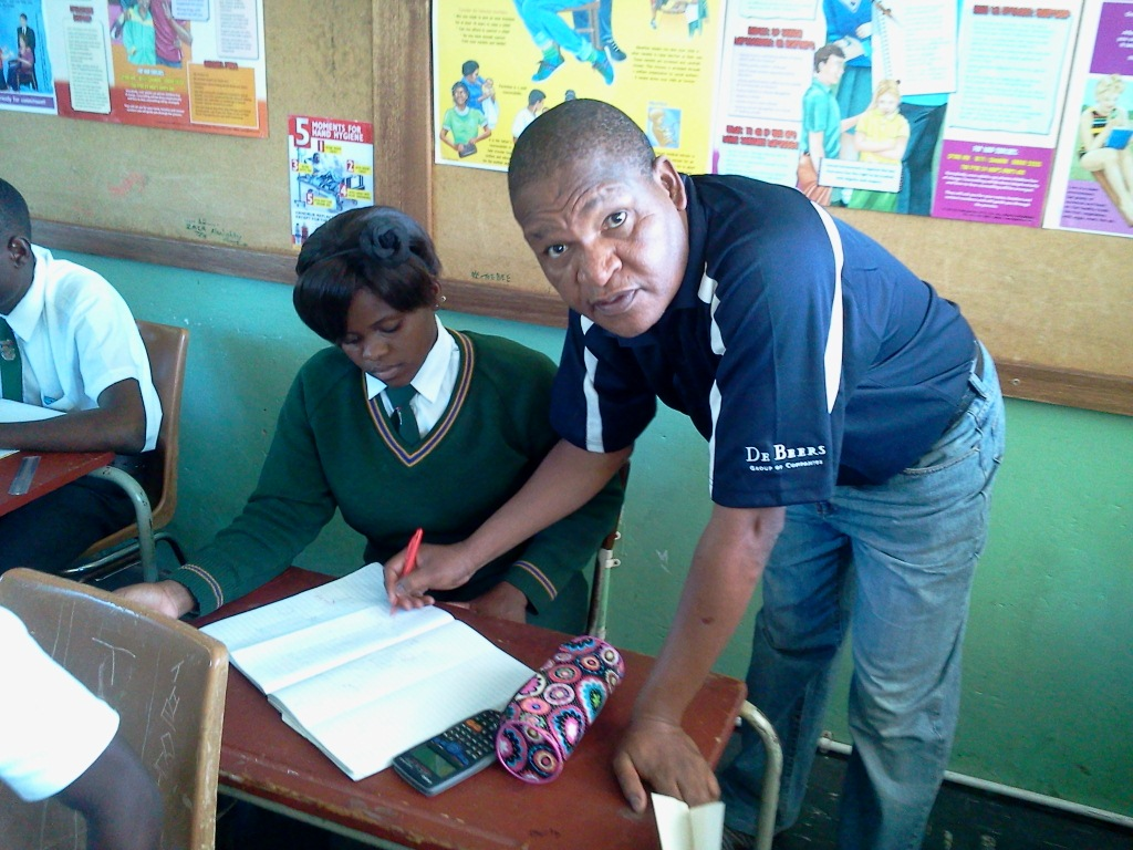 James Moloi, Mathematics teacher tutors a Grade 12 learner from Eric Louw High School